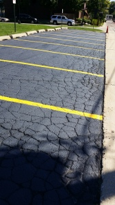 ASPHALT SEALED. HERE THE SEALER WORKS AS A COSMETIC PRODUCT BECAUSE CRACKS WON'T BE FILLED WITH SEALER COAT